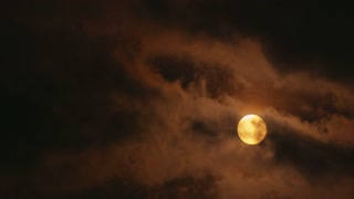 Full Yellow Moon Shining Through Clouds