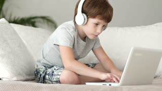 Funny boy in headset sitting on sofa and using laptop