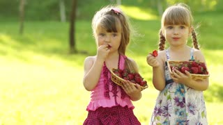 Funny children girl eating strawberries