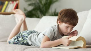 Funny little boy lying on sofa and turning pages of book