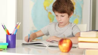 Funny little boy sitting at desk and eating apple
