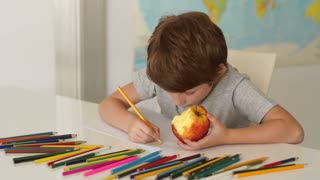 Funny little boy sitting at desk eating apple and drawing