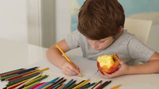 Funny little boy sitting at table and drawing with colored pencils