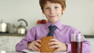 Funny little boy sitting at table and eating burger