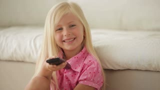 Funny little girl holding remote control smiling and showing thumb up