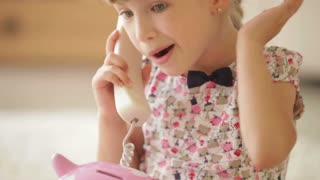 Funny little girl laughing and smiling at camera while talking on phone