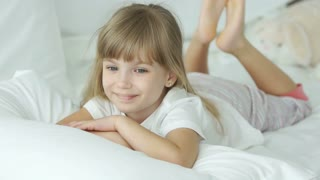Funny little girl lying in bed smiling and laughing