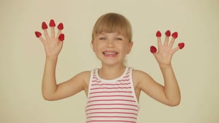 Funny little girl posing with raspberries on top of her fingers