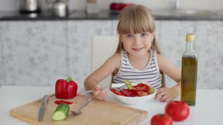 Funny little girl sitting at kitchen table and eating vegetable salad from bowl