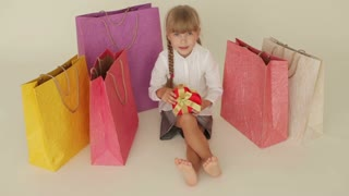 Funny little girl sitting on floor surrounded by shopping bags holding heartshaped box showing thumb up and laughing at camera