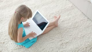 Funny little girl sitting on floor with laptop and smiling at camera