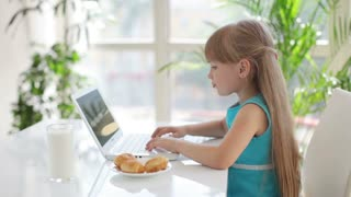 Funny little girl using laptop and eating cakes and looking at camera smiling