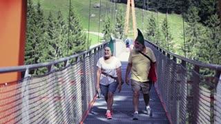 Funny senior couple crossing a suspended bridge