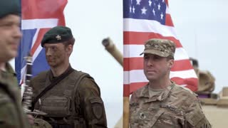 GAIZIUNAI, LITHUANIA - JUNE 18, 2015: Musicians go beside soldiers. Soldiers hold flags during NATO exercise Saber Strike 2015. Editorial use only.