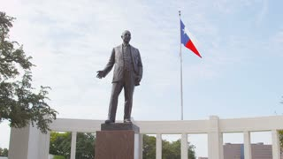 George B. Dealey Statue in Dallas and Texas Flag