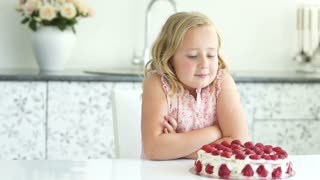 Girl admires cake and smiling