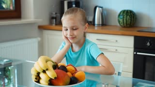 Girl advertises fruits. Child looking at camera and smiling. Zooming
