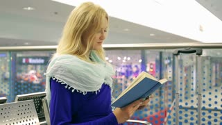 Girl checking time while reading book and hurrying up