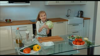 Girl chef in the kitchen holding a cabbage and looking at camera and laughing.  Zooming
