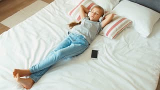 Girl child listening music headphones and lying on the bed. Zooming