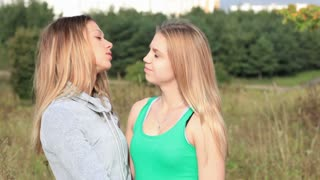 Girl comforting her female friend with kiss and hug. Action on natural background.