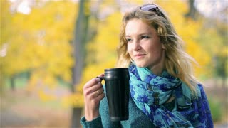 Girl drinking coffee from thermal mug and smiling to the camera
