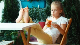 Girl drinking juice and using cell phone and smiling at camera. Girl sitting on the chair. Zooming