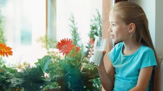 Girl drinking milk and sitting on the windowsill looking in window and laughing at camera. Thumb up. Ok. Zooming