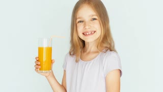 Girl drinking orange juice and smiling at camera. Girl with beautiful blonde hair on a white background. Child nods. Thumb up. Ok. Closeup