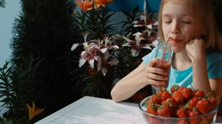 Girl drinking strawberry juice and eating strawberries. Zooming