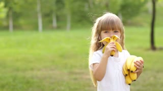 Girl eating a banana and smiles