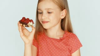 Girl eating a cake with raspberries on the white background. Closeup