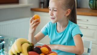 Girl eating apricot. Child sitting in the kitchen table near big plates of fruits. Zooming