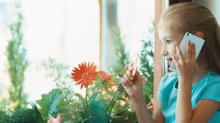 Girl eating biscuits and talking by cell phone. Child sitting on the windowsill and looking out window and looking at camera and smiling. Zooming