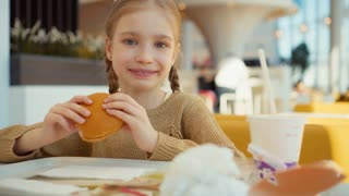 Girl eating burger in the fast food