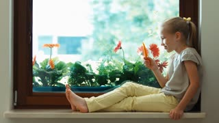 Girl eating carrot and looking out the window. Child sitting on a window sill. Thumb up. Ok. Zooming