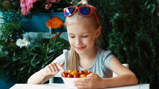 Girl eating cherry tomato and smiling at camera. Thumb up. Ok. Zooming