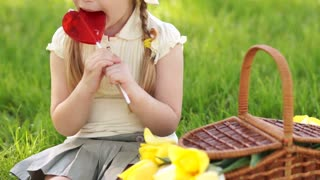 Girl eating lollipop and sitting on the grass