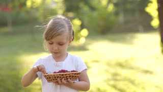 Girl eating raspberry and holding a basket