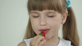 Girl eating strawberries and looking at camera with smile