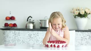 Girl eating strawberry of cake