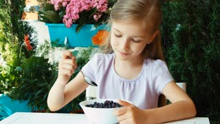Girl eating very tasty blueberries with sugar and nods. Child sitting resting on the table in the garden
