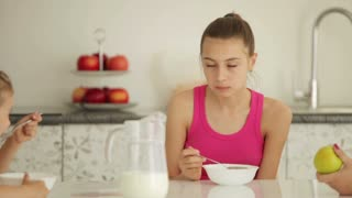 Girl eats cereal with milk and smiling