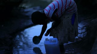 Girl Fills Water Bucket at Watering Hole in Kenya 3