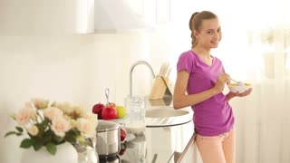 Girl has breakfast standing in the kitchen