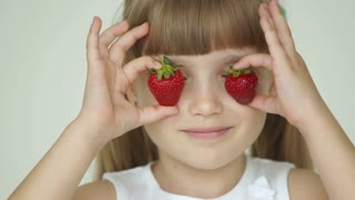 Girl hiding her eyes with two strawberries