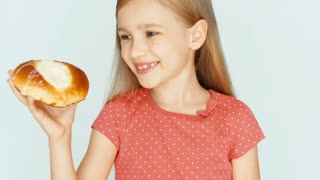 Girl holding a cake with cheese and showing at camera. Child on the white background. Thumb up. Ok. Closeup
