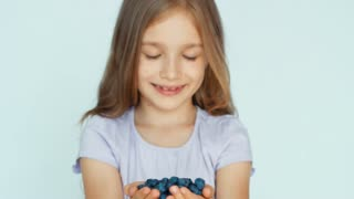 Girl holding in handful blueberry sniffing and showing at camera on the white background. Happy child with fruits. Closeup