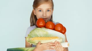 Girl holding vegetables cabbage, corn, tomato celery and laughing at camera. Closeup