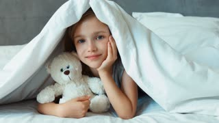 Girl hugging teddy bear under the blanket and smiling at camera. Zooming